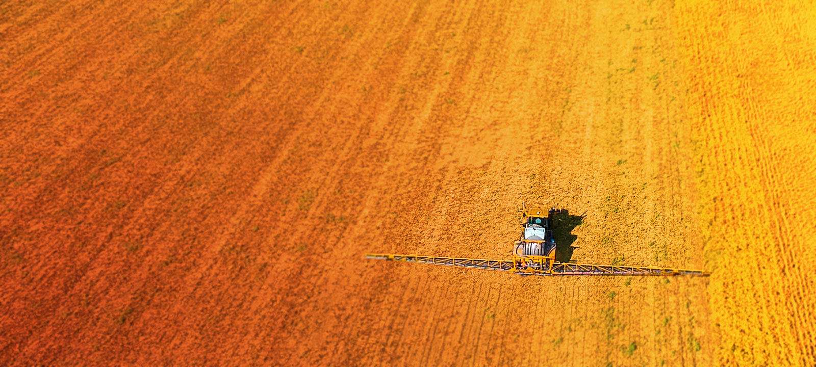 Stylized, blurred overhead view of field and chemical fertilizer spreader tractor