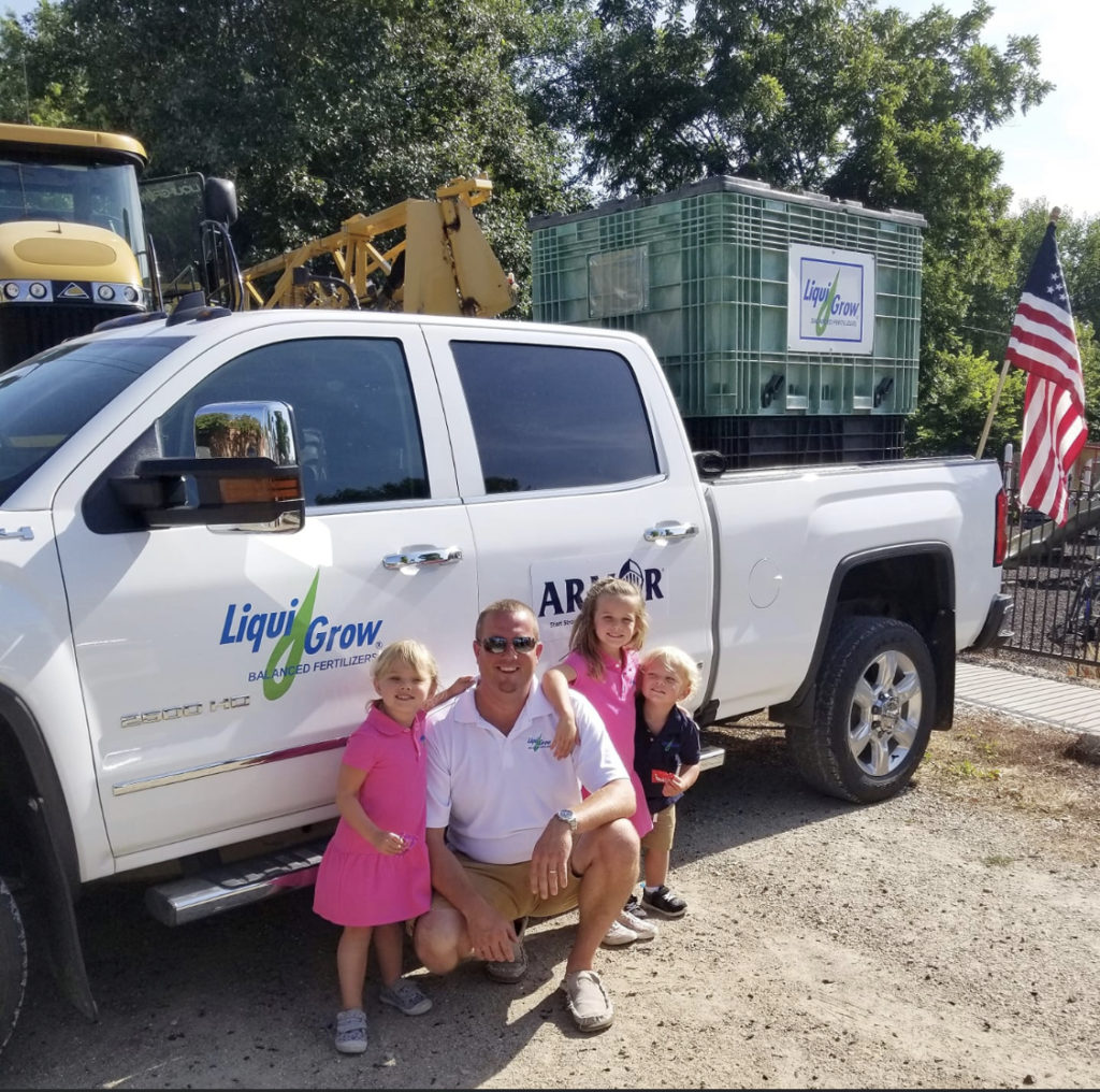 Liqui-Grow employee with kids and parade float