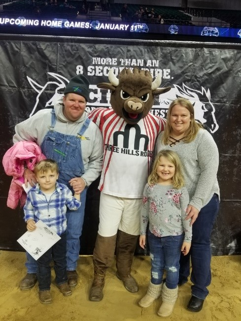 Greg's family standing with a mascot