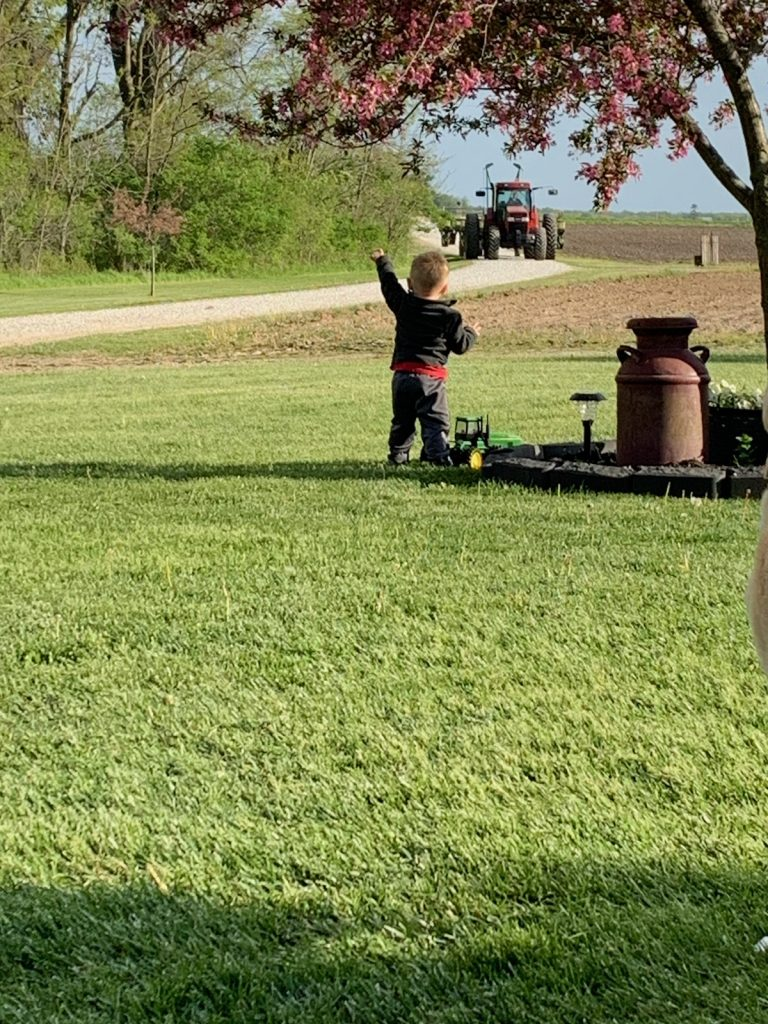 Breann Weaver's son Jaxson waving at Grandpa Mike as he finishes up planting!