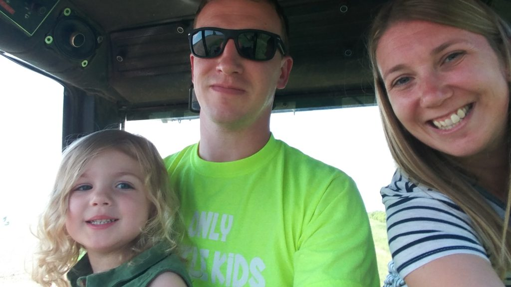 Family of three white farmers sitting in a tractor cab